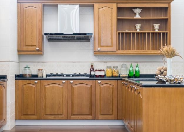 Nowoczesne, jasne, czyste wnętrze kuchni z urządzeniami ze stali nierdzewnej w luksusowym apartamencie.