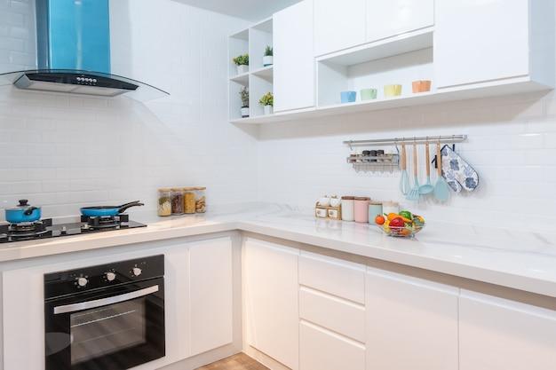 Nowoczesne, jasne, czyste wnętrze kuchni ze sprzętem ze stali nierdzewnej w luksusowym apartamencie.