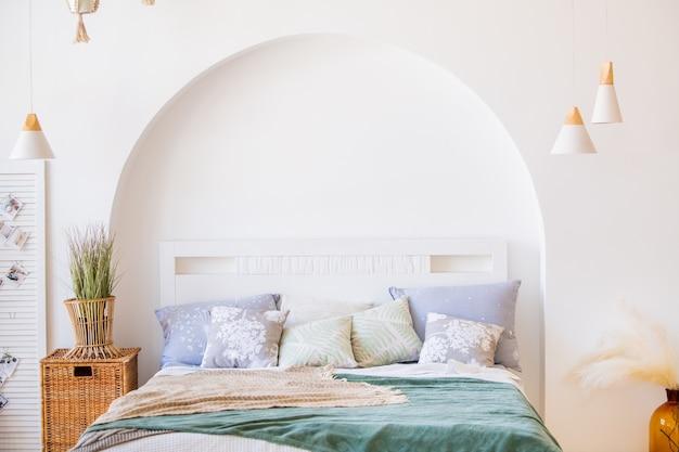 Nowoczesne jasne wnętrze sypialni z łóżkiem, poduszkami i roślinami doniczkowymi oraz ozdobnymi koszami