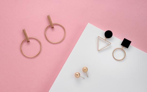 Nowoczesne kolczyki sztyfty na białej i różowej powierzchni