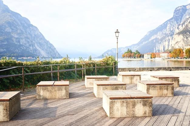 Nowoczesne ławki w nasypie w słoneczny dzień w pobliżu włoskiego jeziora como. drewniana ławka zewnętrzna natura