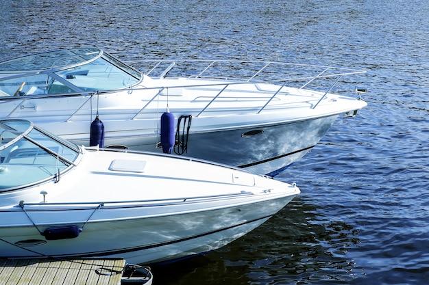 Nowoczesne łodzie motorowe na wodzie. zacumowany na wodzie przy molo