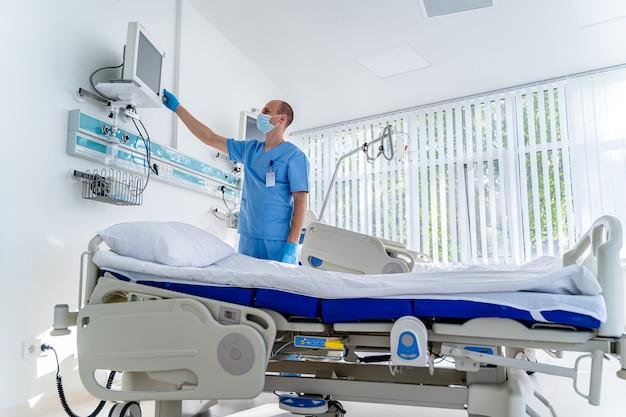 Nowoczesne łóżko medyczne i specjalne urządzenie w nowoczesnym oddziale. lekarz przygotowujący sprzęt dla pacjenta.