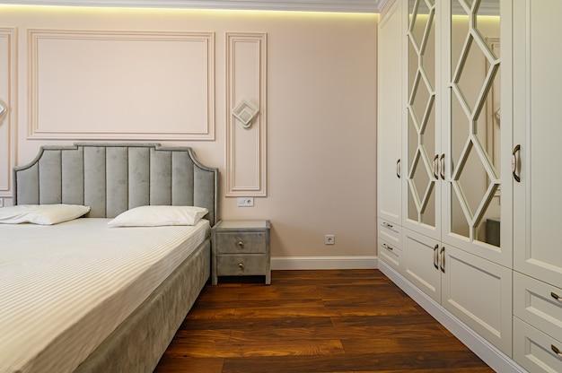 Nowoczesne luksusowe wnętrze sypialni z podwójnym łóżkiem w kolorach beżu i brązu