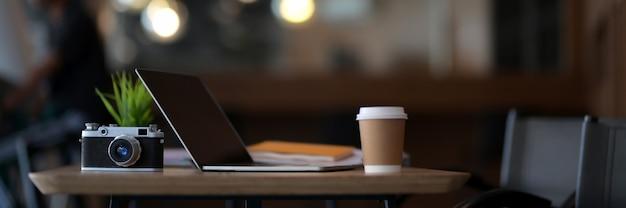 Nowoczesne miejsce do pracy z laptopem, aparatem i materiałami eksploatacyjnymi w kawiarni
