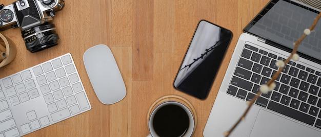 Nowoczesne miejsce do pracy z laptopem, bezprzewodowymi urządzeniami komputerowymi, smartfonem, aparatem i filiżanką kawy
