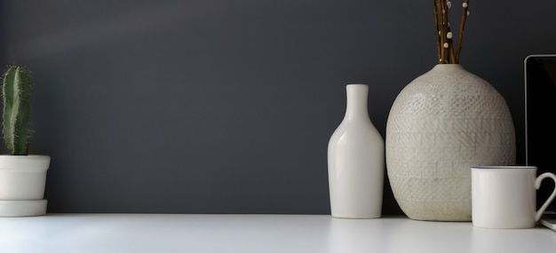 Nowoczesne miejsce do pracy z miejsca kopiowania i ceramiczny wazon na białym stole i szarej ścianie