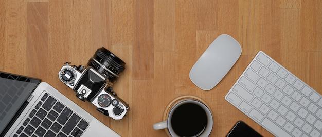 Nowoczesne miejsce do pracy z miejscem do kopiowania, bezprzewodowymi urządzeniami komputerowymi, aparatem, filiżanką kawy i laptopem