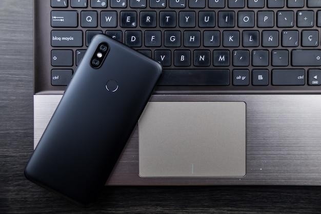 Nowoczesne miejsce na notebooka i smartfona. telefon komórkowy z podwójnym aparatem i czytnikiem linii papilarnych