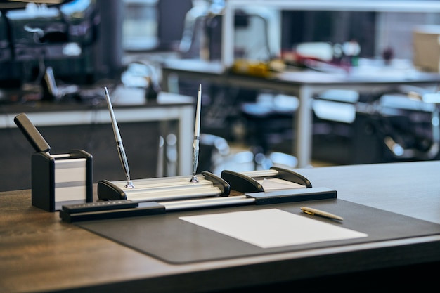 Nowoczesne miejsce pracy biurowej w dużej korporacji. wygodny stół roboczy z papeterią, skórzanym krzesłem komputerowym. szef, szef, przełożony lub szef miejsca pracy firmy.
