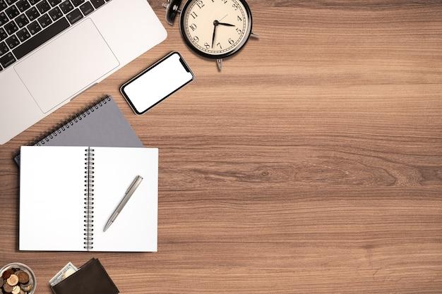 Nowoczesne miejsce pracy drewniane biurko w biurze, widok z góry płaski układ stacjonarnego laptopa i notatki notebooka z miejscem na kopię.