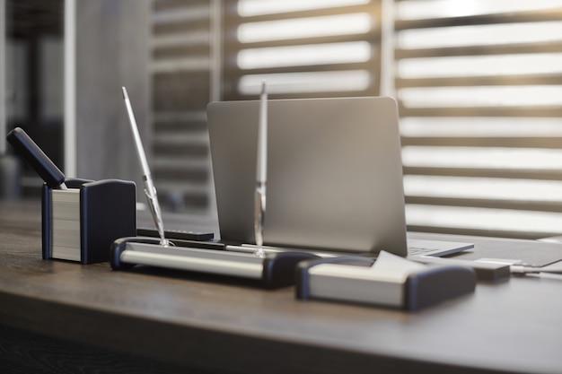 Nowoczesne miejsce pracy w biurze. laptop biznesowy w miejscu pracy dla szefa, szefa lub innych pracowników. notatnik na stole roboczym. biuro dużej korporacji. światło przez pół otwarte żaluzje