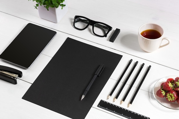 Nowoczesne miejsce pracy z cyfrowym tabletem i telefonem komórkowym, filiżanką długopisu do kawy i pustym arkuszem ...