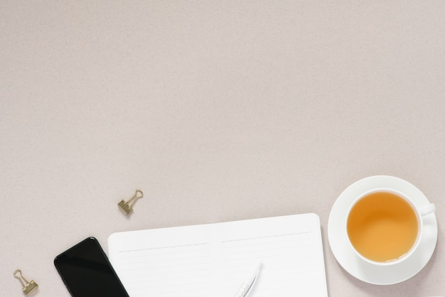 Nowoczesne miejsce pracy z filiżanką herbaty. blat biurowy z pamiętnikiem, długopisem i telefonem. baner pracy z miejsca kopiowania