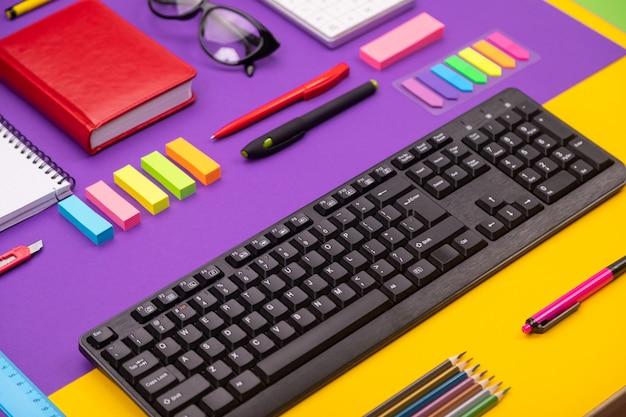 Nowoczesne miejsce pracy z klawiaturą, pamiętnikiem, ołówkami, długopisami i szklankami na pomarańczowo-fioletowym kolorze.