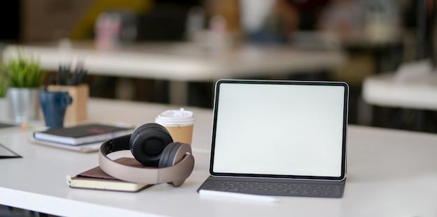 Nowoczesne miejsce pracy z pustym ekranem, słuchawkami nausznymi i artykułami biurowymi