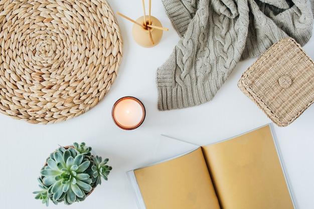 Nowoczesne, minimalistyczne domowe biurko do pracy w stylu boho z notatnikiem, soczystą, dzianinową kratą, świecą, patyczkami zapachowymi, wikliną słomianą i serwetkami na białej powierzchni