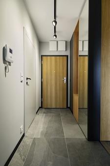 Nowoczesne, minimalistyczne wnętrze hali. białe ściany, drewniane drzwi, lustro na ścianie. szablon.