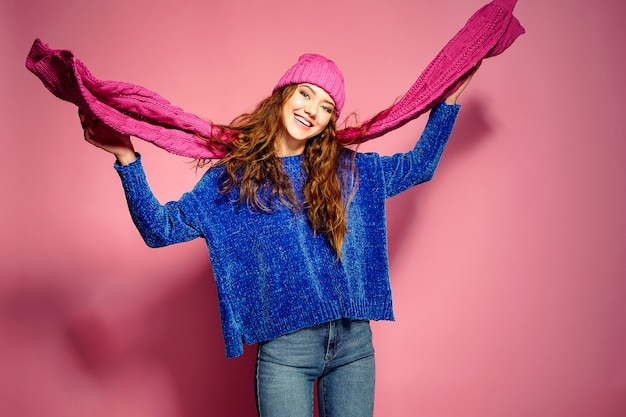 Nowoczesne młoda kobieta ma na sobie niebieski sweter i różowy kapelusz i szalik pozowanie, co sprawia, że zabawny wyraz twarzy.