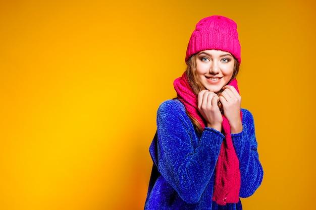 Nowoczesne młoda kobieta ma na sobie niebieski sweter i różowy kapelusz