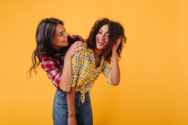 Nowoczesne młode dziewczyny o ciemnych kręconych włosach w świetnym nastroju lubią swobodne rozmowy. wewnątrz portret pięknych kobiet ze śnieżnobiałymi uśmiechami.