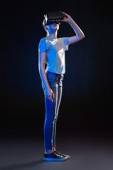 Nowoczesne multimedia. przyjemna śliczna kobieta korzystająca z okularów vr, stojąca na czarnym tle