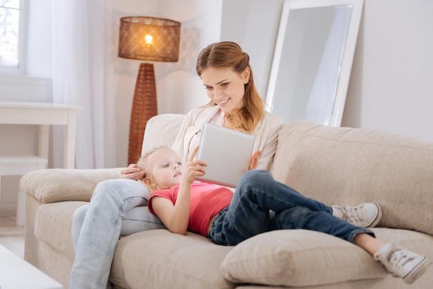 Nowoczesne pokolenie. mądra pozytywna miła dziewczyna leży na nogach matki i używa tabletu podczas grania w gry