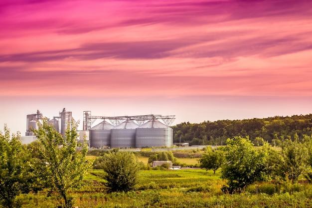 Nowoczesne przedsiębiorstwo w pobliżu lasu rano o wschodzie słońca. letni krajobraz przemysłowy w obszarze przyjaznym dla środowiska