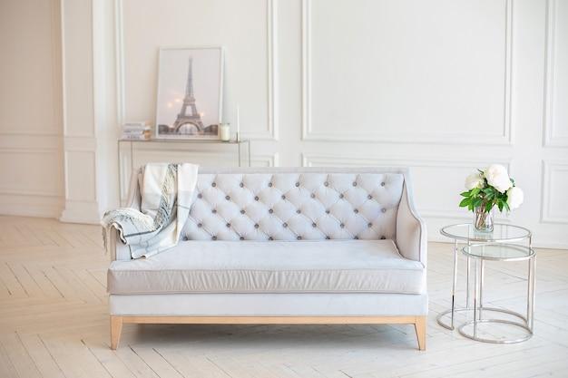 Nowoczesne przestronne minimalistyczne wnętrze salonu z szarą sofą