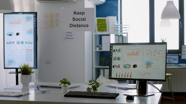 Nowoczesne, puste biuro z plastikowymi przekładkami i plakatem z zachowaniem dystansu społecznego na ścianach. puste wnętrze biznesowej przestrzeni korporacyjnej, w której nikogo nie ma?