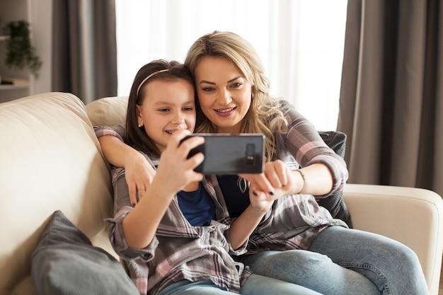 Nowoczesne rodzicielstwo młodej matki z córeczką za pomocą smartfona.