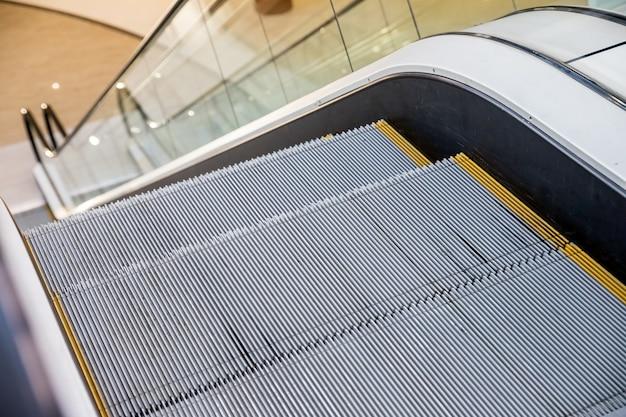 Nowoczesne schody ruchome, szare metalowe, teksturowane stopnie czarna poręcz przezroczysta akrylowa lub plastikowa osłona boczna w centrum handlowym, biurowcu lub na stacji metra