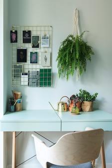 Nowoczesne skandynawskie wnętrze domowego biura ze stołem projektowym, fotelem, akcesoriami biurowymi, dużym oknem i roślinami