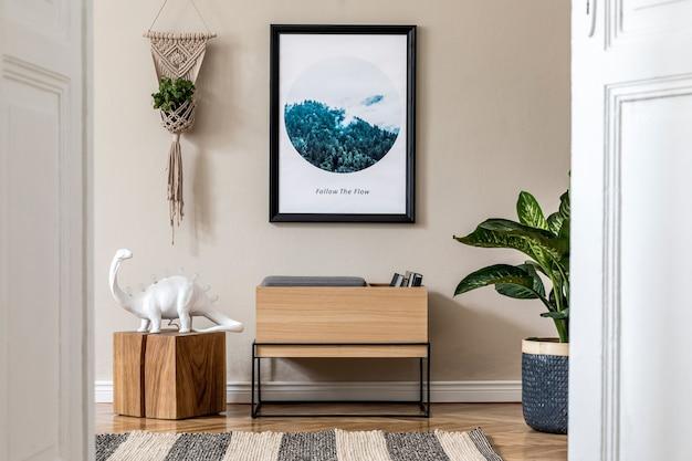 Nowoczesne skandynawskie wnętrze salonu z czarną makietową ramą na plakat, designerską szafką, roślinami, stołem, lampą, makramą i eleganckimi akcesoriami osobistymi