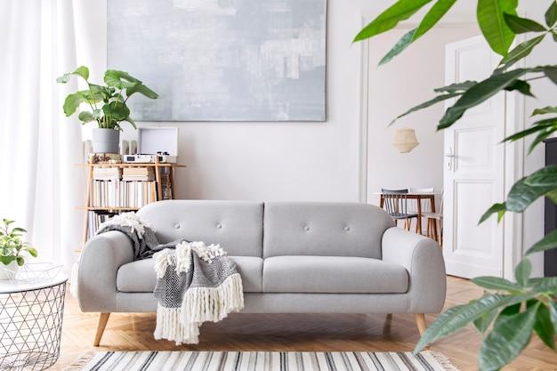 Nowoczesne skandynawskie wnętrze salonu z designerską sofą, eleganckim kocem, stolikiem kawowym, regałem, roślinami i brązowym drewnianym parkietem