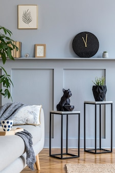 Nowoczesne skandynawskie wnętrze salonu z szarą sofą, pledami, marmurowymi taboretami, roślinami, świecą, zegarem, książkami, ramkami i eleganckimi akcesoriami osobistymi w stylowym wystroju domu.