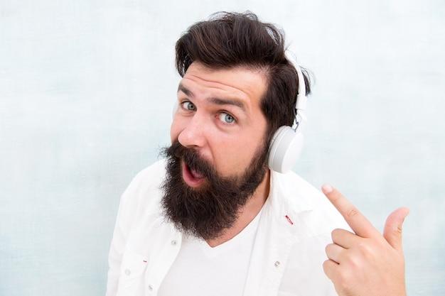 Nowoczesne słuchawki bezprzewodowe. elektroniczne utwory muzyki tanecznej. muzyka instrumentalna. słuchawki brodaty mężczyzna. ciesz się każdą nutą. technologia aktywnej redukcji szumów. hipster słuchać muzyki stereo słuchawki.