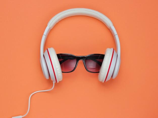 Nowoczesne słuchawki z okularami przeciwsłonecznymi na koralowym tle. koncepcja kreatywnej muzyki. styl retro.