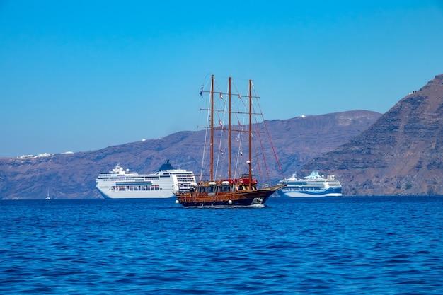 Nowoczesne statki wycieczkowe i stary żaglowiec u wybrzeży santorini