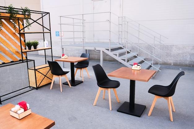 Nowoczesne, stylowe wnętrze ulicznej kawiarni lub restauracji. puste stoły i krzesła na zewnątrz na ulicy