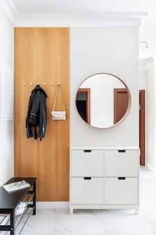 Nowoczesne, świeże białe wnętrze przedpokoju. drzwi wejściowe, drewniany wieszak z wiszącymi ubraniami i torebka damska. w pobliżu drzwi znajduje się szafka na buty i okrągłe lustro na ścianie