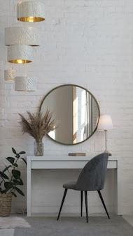 Nowoczesne szare aksamitne krzesło, biurko, okrągłe lustro i lampa stołowa oraz akcesoria domowe i żyrandol