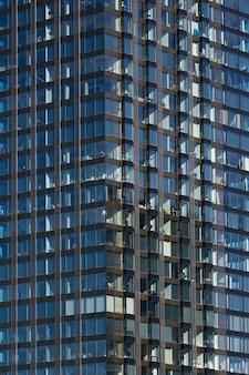 Nowoczesne szklane wieżowiec tło z odbiciem nieba i chmur