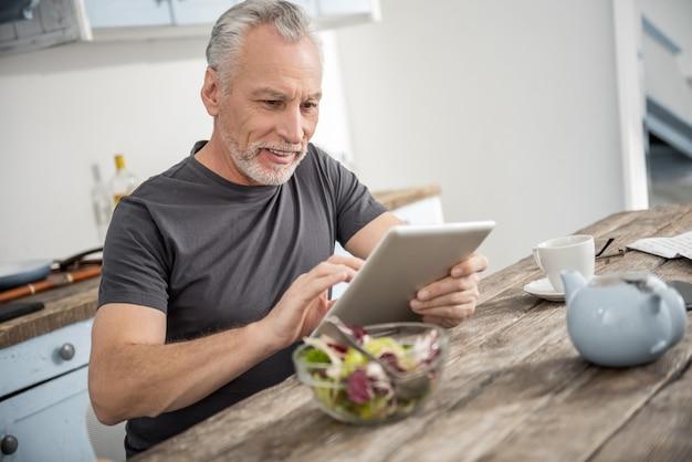 Nowoczesne technologie. przystojny brodaty mężczyzna z uśmiechem na twarzy i patrząc na swój gadżet będąc w kuchni
