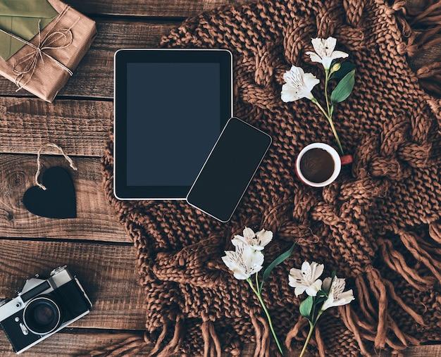Nowoczesne technologie. ujęcie pod wysokim kątem z dzianinowego szalika, kwiatów, filiżanki kawy, pudełka na prezenty,
