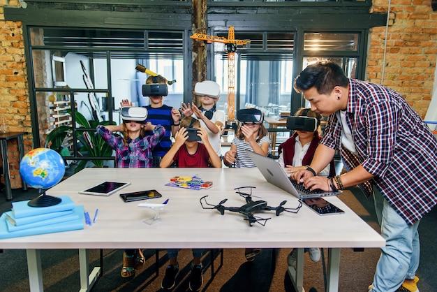 Nowoczesne technologie w inteligentnej szkole. sprytni uczniowie rasy kaukaskiej używają okularów do wirtualnej rzeczywistości w celach edukacyjnych.