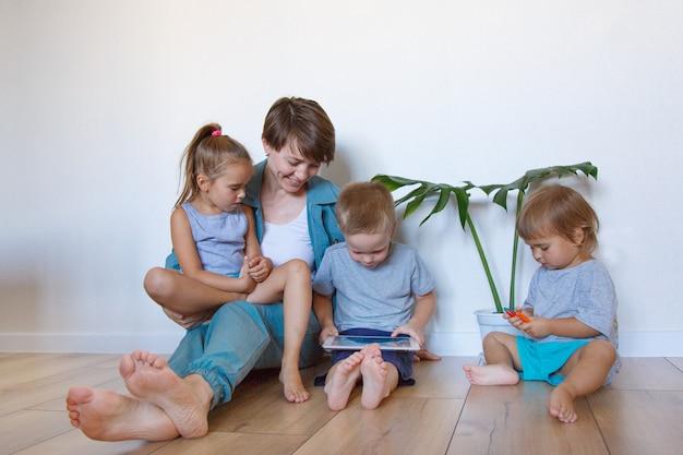 Nowoczesne technologie w życiu codziennym kobieta i dzieci patrzą na tablet na podłodze. hobby i rekreacja z gadżetami. rodzinne wakacje, spędzanie czasu mama i syn razem w domu.