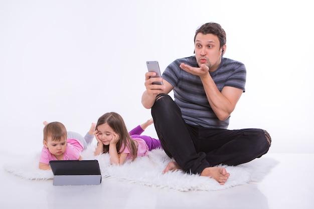 Nowoczesne technologie w życiu codziennym: mężczyzna rozmawia przez telefon przez zestaw słuchawkowy, dzieci oglądają kreskówkę na tablecie. hobby i rekreacja z gadżetami. rodzic z dziewczynami na podłodze