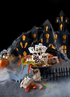 Nowoczesne tło halloween. halloweenowy batonik: śmieszne potwory zrobione z ciastek z czekoladą i duchami marshmelow z bliska na stole