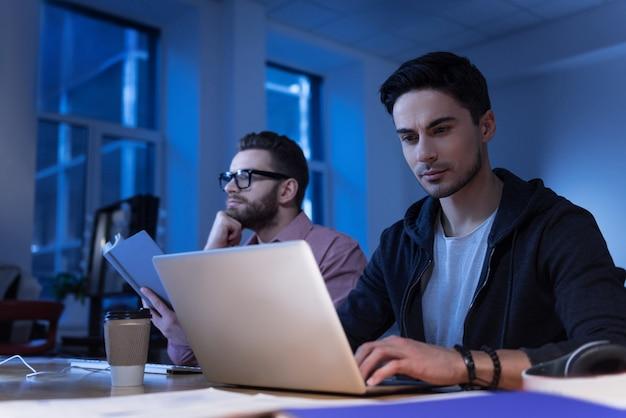 Nowoczesne urządzenie. pozytywny inteligentny programista brunetka pisze i patrzy na ekran laptopa podczas pracy w biurze